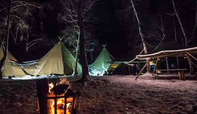 Picture of lavvo / tipi construction for an event in mids of forrest in night-time, fire lit in front. Aktiv i lom.